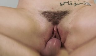A tattooed chick with large natural tits is opens up her hairy pussy