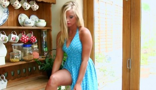 Blonde in polka dot halter attire spreads her legs wide and masturbates
